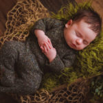 baby sleeping in a wooden box with sleepy outfit on