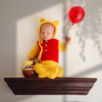 baby sitting on a shelf dressed as winnie the pooh baby was safe laying on floor on his back for this image