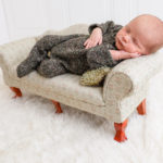 baby sleeping on a miniature couch