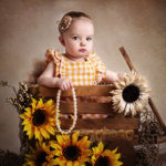 toddler girl in wooden wagon with sunflowers